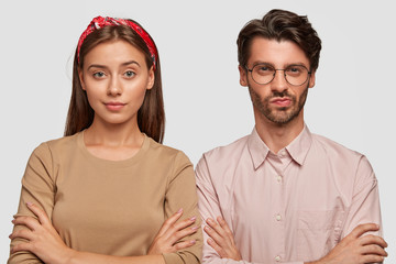 Wall Mural - Horizontal shot of pretty European female and male students have serious confident expressions, keep hands crossed, wait for exam results, wear stylish clothing, isolated on white background