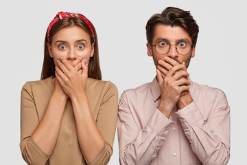 Impressed two young attractive female and male loose speech from fright, cover mouthes with both palms, being shocked by negative news, stand closely to each other, isolated over white background