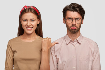 Horizontal shot of happy young female with pleased expression indicates at her offended boyfriend, express different emotions, stand together against white background. People and emotions concept