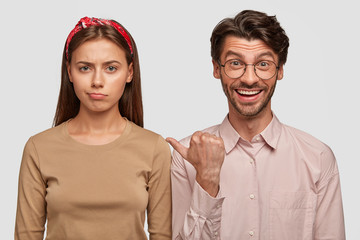 Wall Mural - Displeased European female being abused after quarrel with boyfriend who indicates at her with positive expression, dressed casually, isolated over white background. Two best friends indoor.