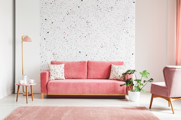 Real photo of a pink, velvet sofa, plant, coffee table with pot and cups on a lastrico wall in a living room interior