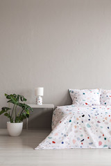 Real photo of a plant, bedside table with a lamp and patterned sheets on a bed set on an empty wall in a bedroom interior. Place for your painting/poster/graphic