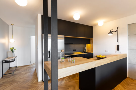 Lights in black kitchen interior with bright modern countertop and wooden floor. Real photo