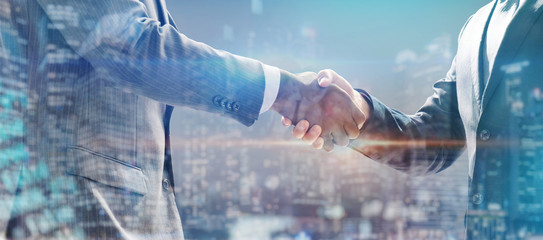 handshake of business people with skyscrapers background and finance and marketing business conclusion
