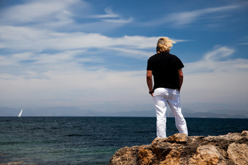 A blond man on his back with white trousers and a black T-shirt observes a Mediterranean sea landscape from the rocky coast.