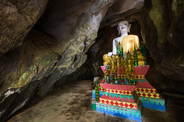 Several Buddha statues on altar inside the Tham Hoi Cave near Vang Vieng, Vientiane Province, Laos.