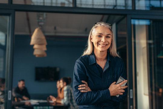 Smiling senior woman standing in office doorway
