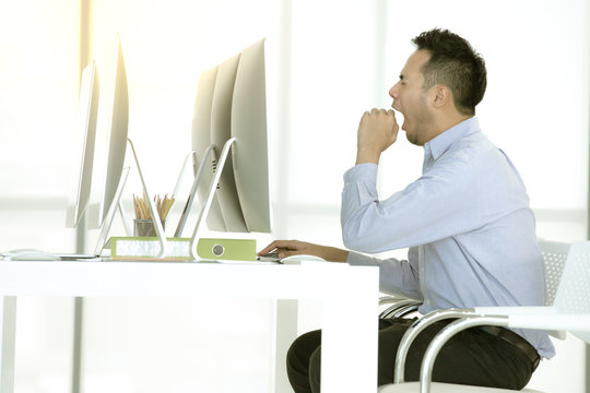 Young Asian businessman is sitting and yawn in  modern office.