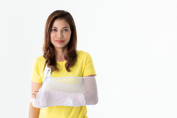Arm broken Asian woman with arm sling supported on her hand, concept for injured by accident and healthcare. Studio shot a white background.