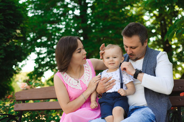 family, parenthood, adoption and people concept - happy mother, father and little boy walking in summer park