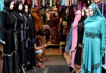 A vendor of Islamic clothing uses his mobile phone in a market stand in Quiapo