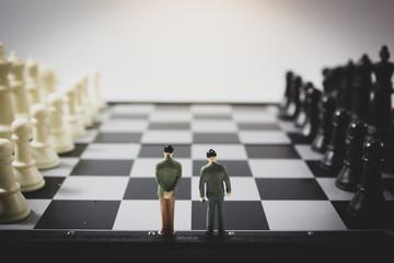 Closeup black view miniature businessman on chess board.