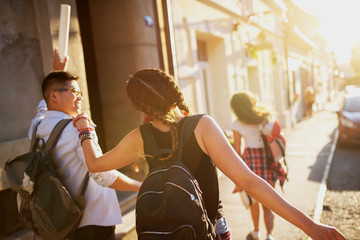 Young excited student tourists walking in a city streets and having fun on a hot summer day.