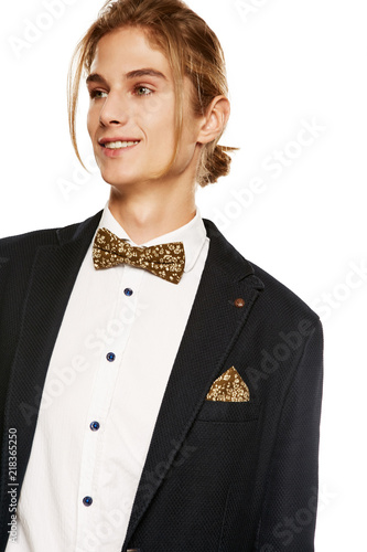 8d80897e49 A young man in a black suit jacket and button up shirt, accessorized with a  khaki green floral bow tie and matching pocket square.