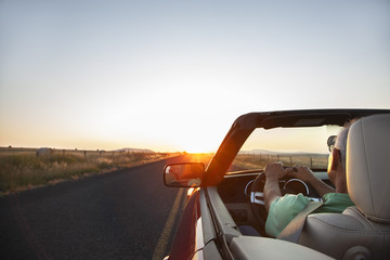 A senior Hispanic man at the wheel of his convertible sports car at sunset in eastern Washington State, USA.
