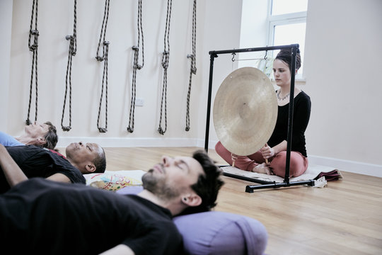 Woman using a gong during a sound therapy session and three people lying on their backs relaxing.