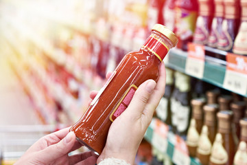 Foto op Aluminium Kruiderij Buyer hands with bottle of chilli sauce in store
