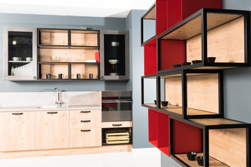 interior of modern clean light kitchen with kitchen counters and red shelves