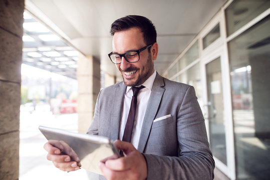 Young modern businessman standing outside looking at his digital tablet with satisfaction on his face.Good day at job.