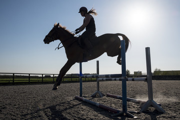 Silhouette of female rider jumping a hurdle on a showjumper horse.