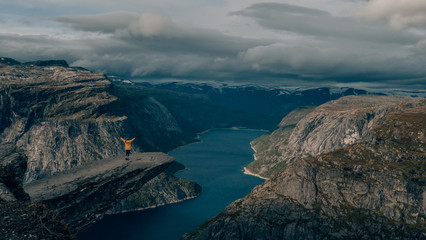 happy girl with wanderlust in norway at trolltunga
