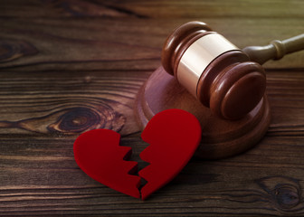 two halves of the heart, a hammer of the judge on a wooden background. family law, divorce and conflict.