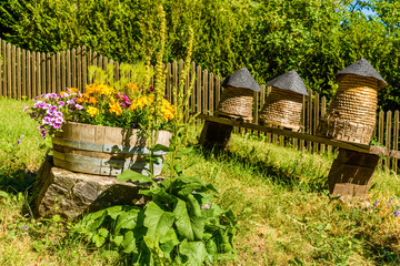 Three small beehives and a flowerpot with colorful flowers. The garden is hilly so the beehives and the flowerpot leans a bit. Summertime in the garden.