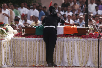 A soldier adjusts the Indian national flag on the coffin of former Prime Minister Atal Bihari Vajpayee before his cremation in New Delhi