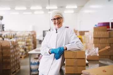 Portrait of a smiling female worker in sterile clothes leaning on a packages.