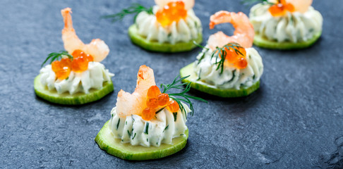 Papiers peints Entree Appetizer canape with red caviar, shrimp and cream cheese on stone slate background close up. Delicious snacks, sandwiches