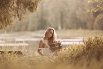 Sensual young woman with beautiful breasts sitting naked or nude by the lake at sunset and holding picnic basket