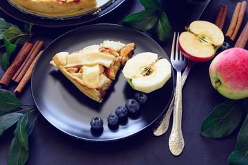 American tradition apple pie with apples, blueberry and cinnamon decorated apple leaves on dark wooden background. Flat lay. Still life. Toned