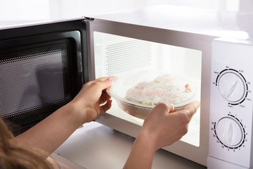 Woman Heating Food In Microwave Oven