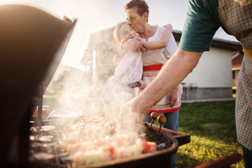 Happy grandmother and granddaughter are hugging in front of a barbeque.