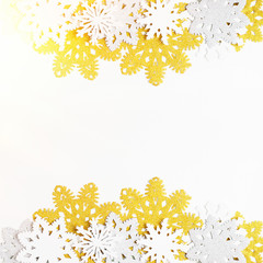 Golden, silver and white paper snowflakes on white background. New year, christmas concept. Text space