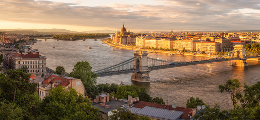 Amazing panorimic view before sunset with the building of Hungarian Parliament in Budapest lit by sun