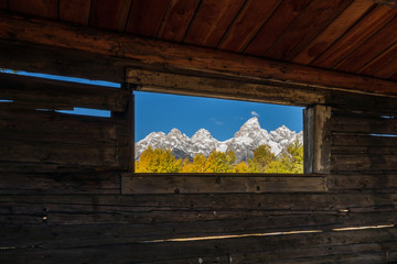 Tetons in Autumn Through an Old Cabin Window
