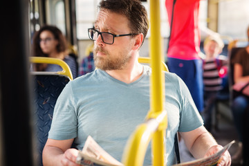 Serious man is holding newspapers in his hand while sitting in a bus.