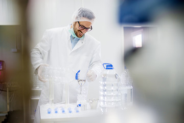 Laboratory employee in protective wear testing new products.