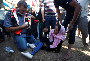 Wounded Palestinian girl reacts during a protest demanding the right to return to their homeland at the Israel-Gaza border, in Gaza