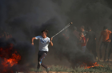 Palestinian demonstrator uses a sling to hurl stones at Israeli troops during a protest demanding the right to return to their homeland at the Israel-Gaza border, in Gaza