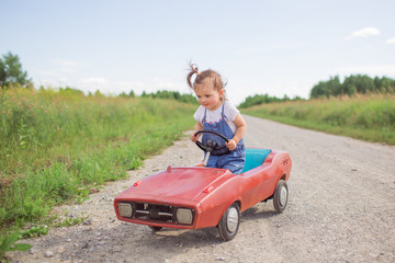 A sweet girl runs a children's car on the road in the summer