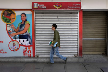 A man walks past a closed automated teller machine (ATM) outside a Banco del Tesoro branch in Caracas