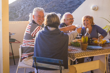 cheerful group of adult couples having fun together cheers with wine eating a grill food in outdor terrace leisure activyt at home. celebrating caucasian people - laughing and funny evening in summer