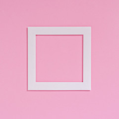Empty white frame on a pink textured paper background, top view. Flat lay