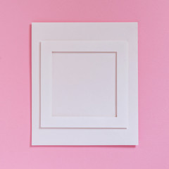 Empty white frame on a white paper on textured pink background, top view. Flat lay