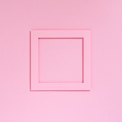Empty pink frame on a pink textured paper background, top view. Flat lay