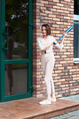 the girl stands at the closed door of the store and tries to break it with a baseball bat