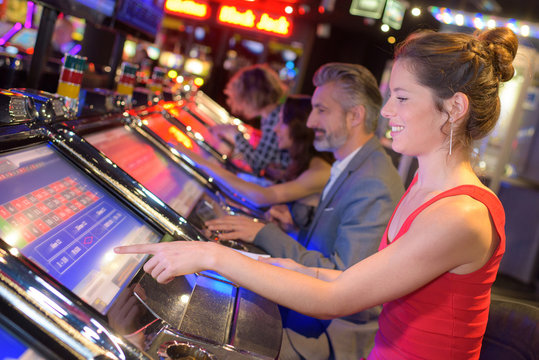 happy woman sitting at slot machine in casino parlour