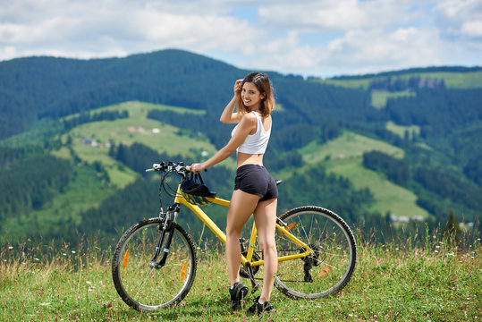 Smiling sexy woman rider posing with yellow mountain bicycle, enjoying sunny day. Mountains, forests on the blurred background. Outdoor sport activity, lifestyle concept